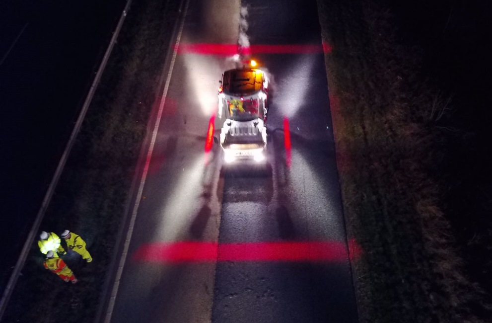 Colas Safety Exclusion Zone marked with red and blue lighting, roadworks at night with plant vehicle and workers.